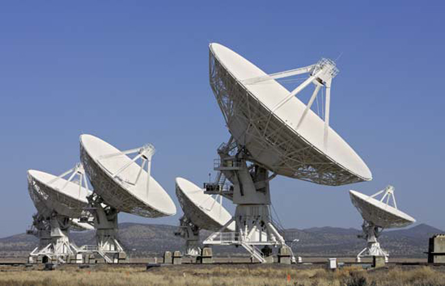 Giant radio telescopes search for extraterrestrial life.